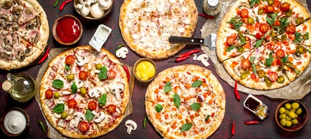 variety of pizzas with sauces. On a rustic background.
