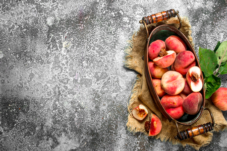 Fresh peaches in a bowl . On a rustic background.