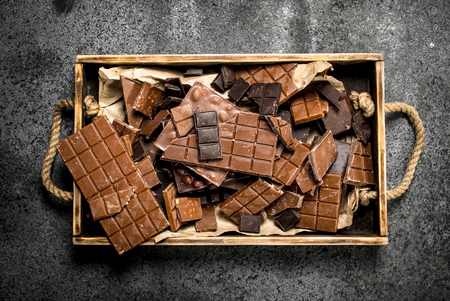 Broken chocolate bars on wooden tray. On a rustic background. Archivio Fotografico