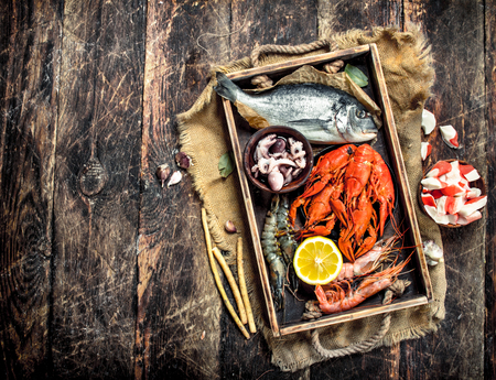Seafood in an old tray. On a wooden background. Standard-Bild