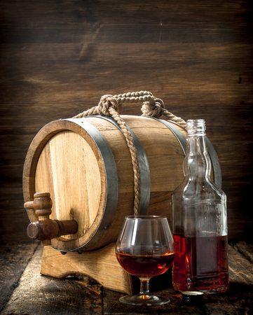 Cognac in a barrel with a glass. On a wooden background. Stock Photo