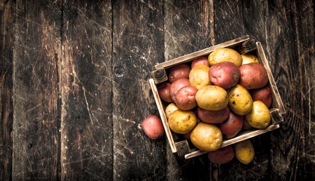 Fresh potatoes in a wooden box. On a wooden background.