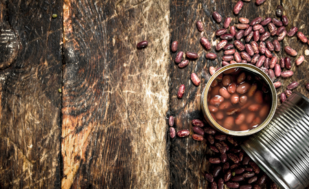Canned red beans in tin cans. On a wooden background.