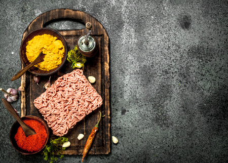 Meat stuffing with spices and herbs on a wooden board. On a rustic background.