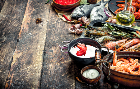 Different seafood with shrimps and red caviar. On a wooden background.