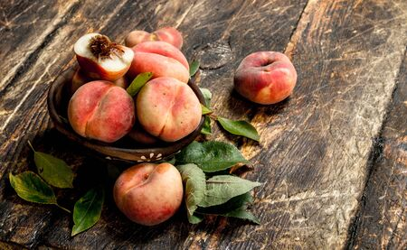Fresh peaches in a bowl. On a wooden background.