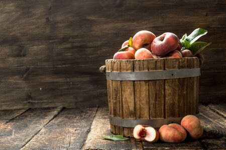 Fresh peaches in a wooden bucket. On a wooden background. Фото со стока