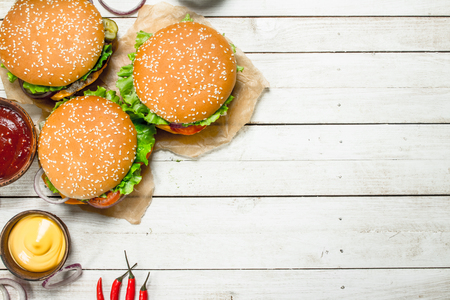 Burgers with fresh beef, cheese and vegetables. On a white wooden background.