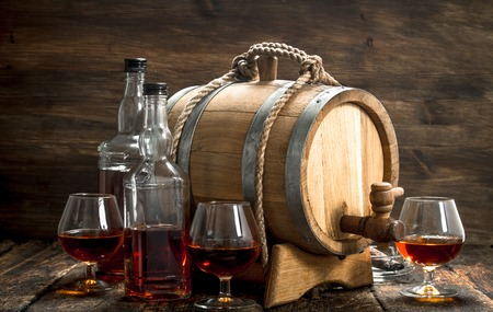 barrel with a long cognac and glasses. On a wooden background. Фото со стока