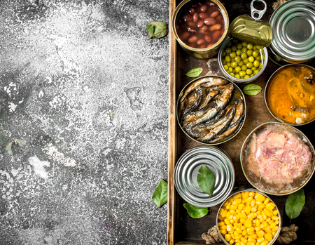 Various canned products in tin cans on a wooden tray. On a rustic background.
