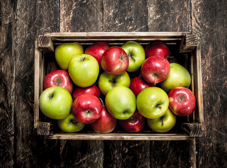 box with fresh red and green apples. On a wooden background. 版權商用圖片