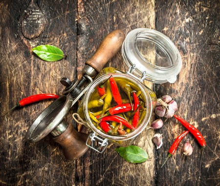 Marinated hot chili peppers with seamer. On a wooden background. Stock Photo
