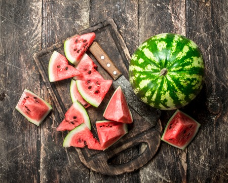 Sliced slices of ripe watermelon on a board. On a wooden background.