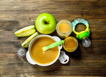 Baby food. Baby puree from green apples. On a wooden background. Stock Photo