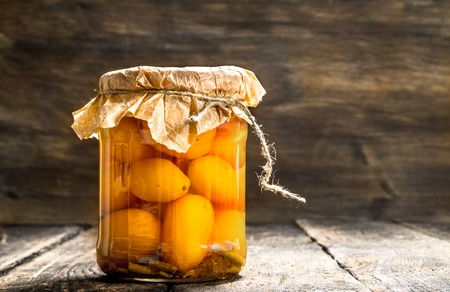 Preserves tomatoes in glass jar . On a wooden background.