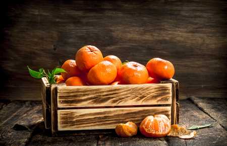 Ripe mandarins in an old box. On a wooden background. Stockfoto