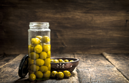 Pickled olives in glass jar and wooden bowl. On a wooden background. Banco de Imagens