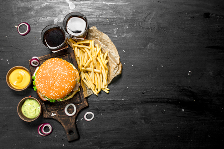 Street food. Fresh burger with cola, fries and sauces. On the black chalkboard.