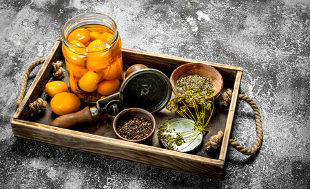 Pickled tomatoes with spices, herbs and seamer on a wooden tray. On a rustic background.