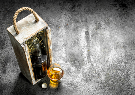 Bottle with cognac and a glass. On a rustic background.