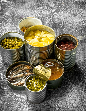 Various canned foods with meat, fish, vegetables and fruits in tin cans. On a rustic background. Stock fotó