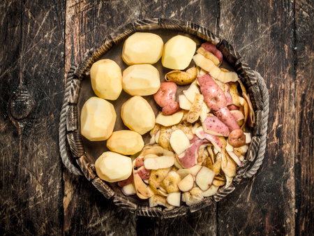 Peeled fresh potatoes on a tray. On a wooden background.