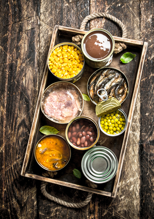 Various canned fruits, vegetables, fish and meat in tin cans on old tray. On a wooden background Archivio Fotografico