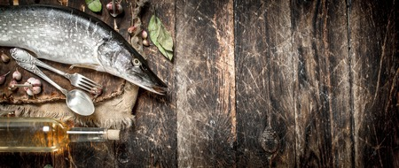 Fresh pike with spices and white wine. On a wooden background.