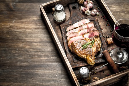 Beef grill with red wine. On a wooden table.