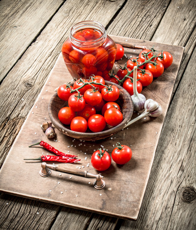 Pickled tomatoes with garlic and spices. On a wooden table.