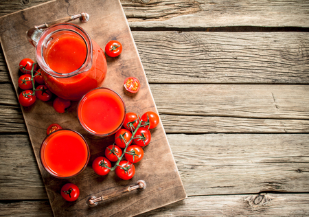 Fresh tomato juice. On a wooden background. 免版税图像