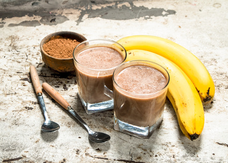 Smoothie with cocoa and banana. On rustic background.