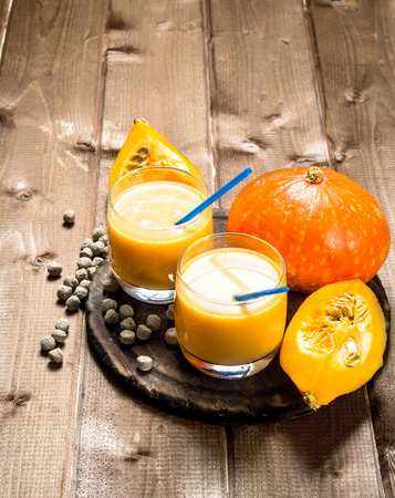 Pumpkin smoothie in glasses . On a wooden table.