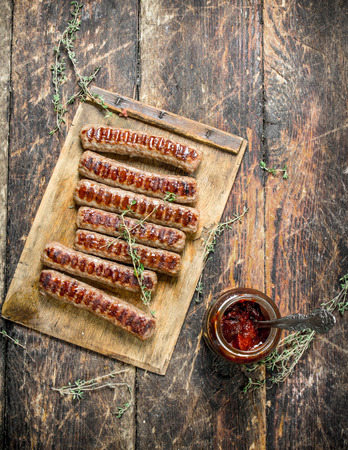 Grilled sausages with sauce. On a wooden background.