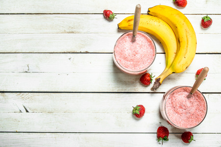 Berry smoothie with banana. On a white wooden background.