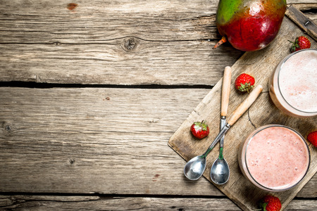 Fresh berry smoothie. On a wooden background.