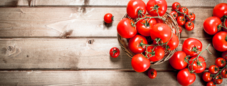 Ripe tomatoes in a basket. On a wooden background.