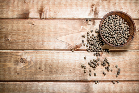 Black pepper in the bowl. On a wooden background.