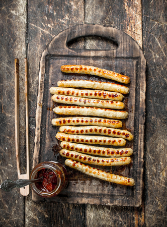 Grilled sausages with tomato sauce. On a wooden background.
