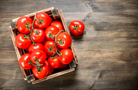 Fresh tomatoes in a box. On a wooden table.