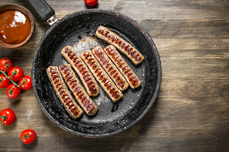 Fried sausages in a pan with sauce. On a wooden background.
