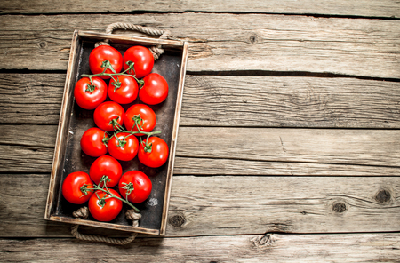 Fresh tomatoes in a wooden tray. On a wooden background.