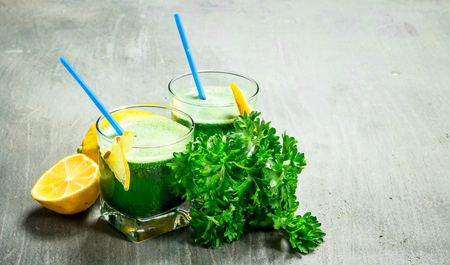 Healthy smoothie with lemon and parsley. On rustic background. 스톡 콘텐츠