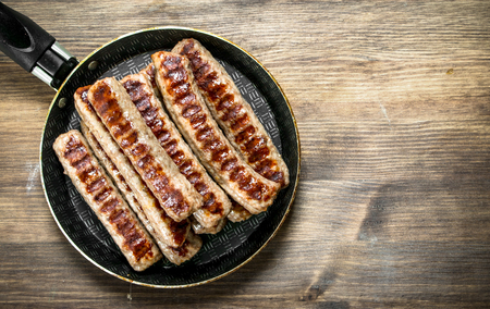 Fried sausages in a frying pan. On a wooden table.