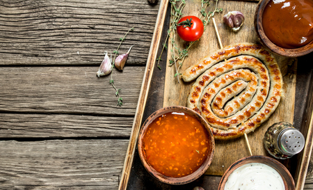 Grilled sausage and sauce. On a wooden background.