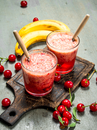 Berry smoothie with banana. On rustic background.