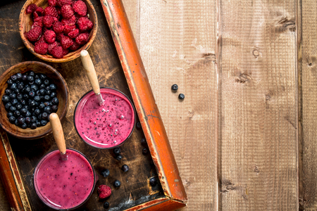 Berry smoothie in glasses . On a wooden background.