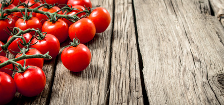 Fresh ripe tomatoes. On a wooden background. 스톡 콘텐츠