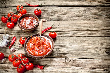Tomato sauce with spices. On a wooden background.