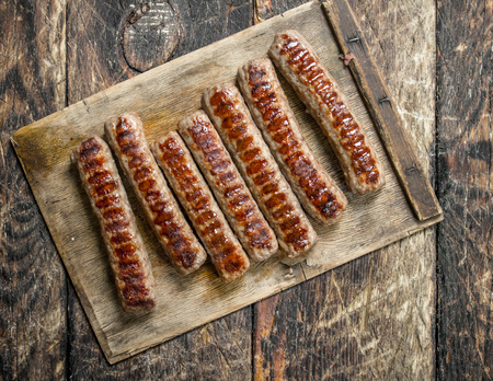 Grilled sausages on a wooden table.